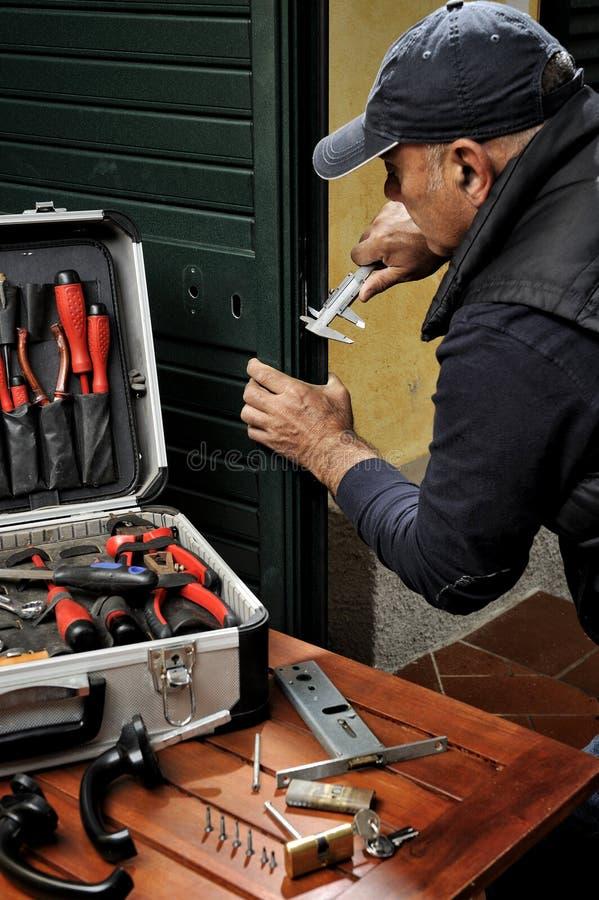 Плотник работая замена замка двери стоковое изображение rf