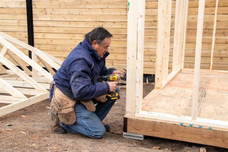 Плотник работая на деревянной структуре стоковое изображение