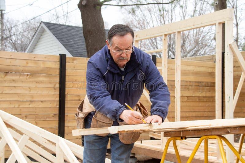 Плотник работая на деревянной структуре стоковые фото