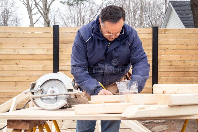 Плотник работая на деревянной структуре стоковая фотография