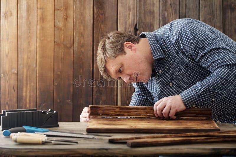 Плотник работая с инструментами на деревянной предпосылке стоковое изображение rf
