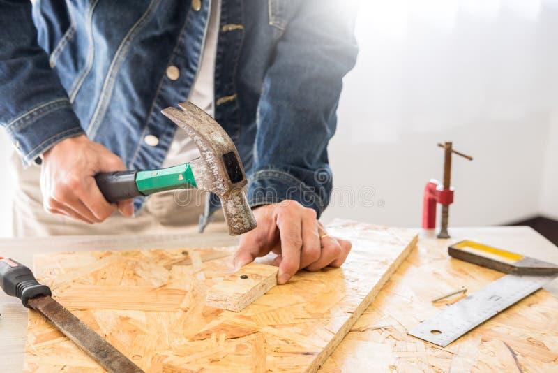 Плотник работая тщательно смотрящ планы работает в плотничестве Он успешный предприниматель на его рабочем месте бить a молотком стоковые изображения rf