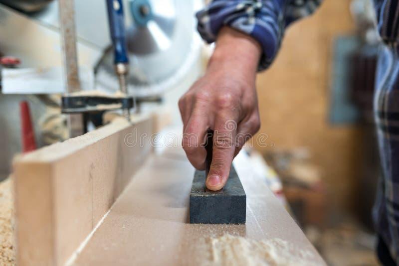Плотник точит зубило в небольшой мастерской, стоковые фото