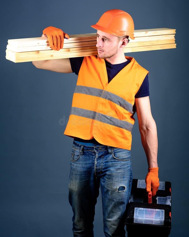 Плотник, woodworker, лейборист, построитель на занятой стороне носит деревянные балки на плече Человек в шлеме, владениях трудной стоковая фотография
