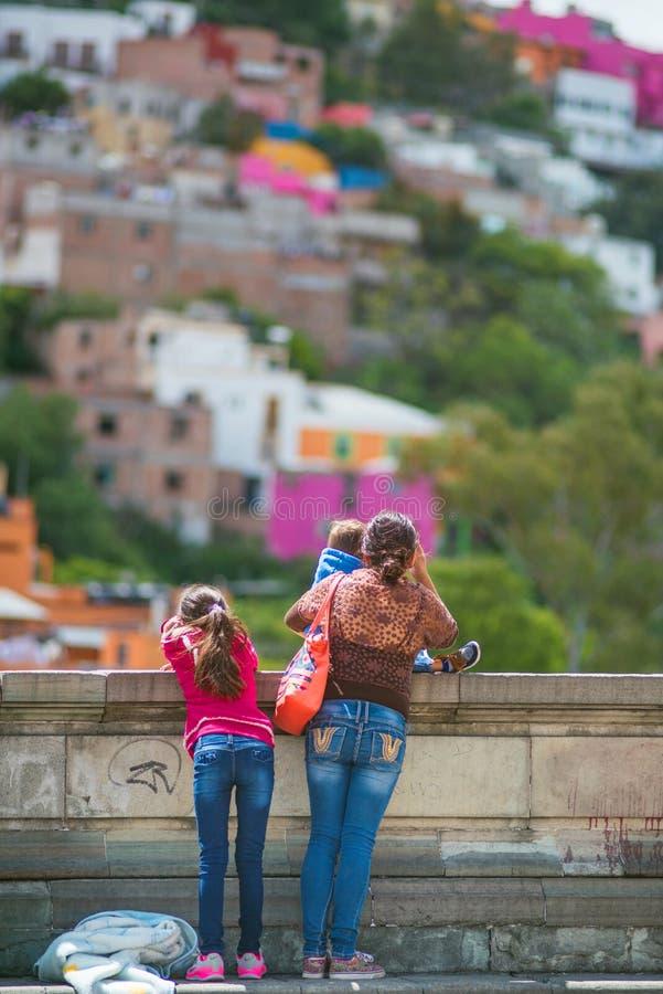 Плохая мать и дети ища надежда в старом мосте, Гуанахуате, Мексике, Америке стоковое фото rf