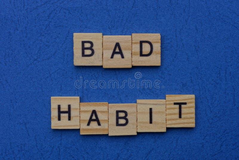 Плохая привычка из коричневых деревянных букв стоковые фотографии rf