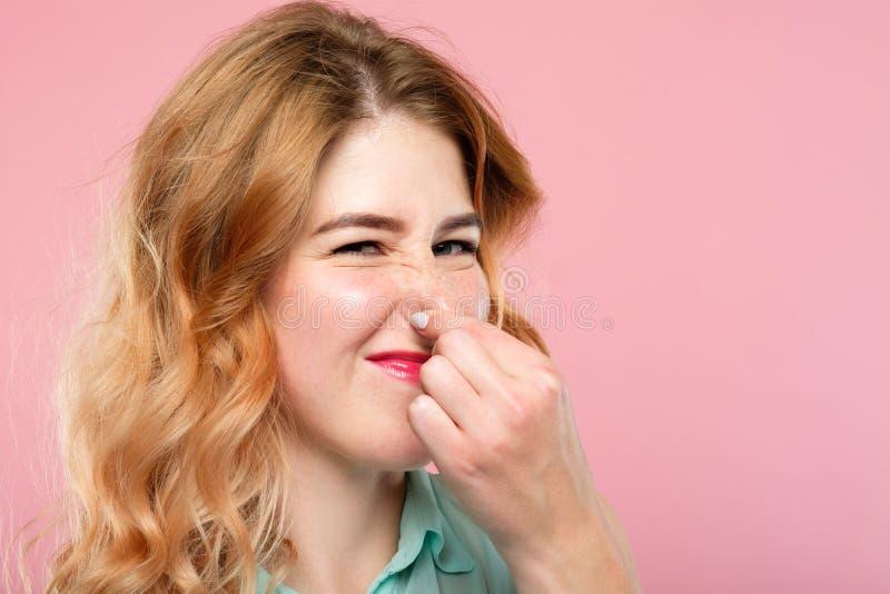 Плохая прогоркловатая женщина запаха запаха держа нос гримасничая стоковое изображение rf