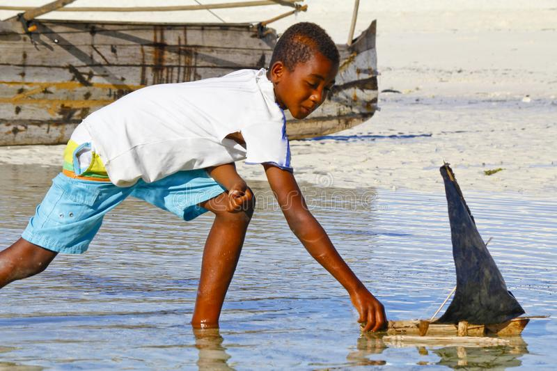 Плохой малагасийский мальчик играя с ручной работы кораблем стоковое изображение