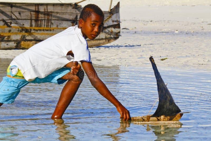 Плохой малагасийский мальчик играя с ручной работы кораблем стоковые изображения