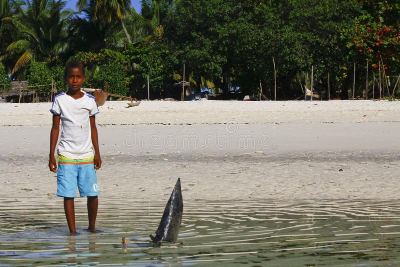 Плохой малагасийский мальчик играя с ручной работы кораблем стоковое фото
