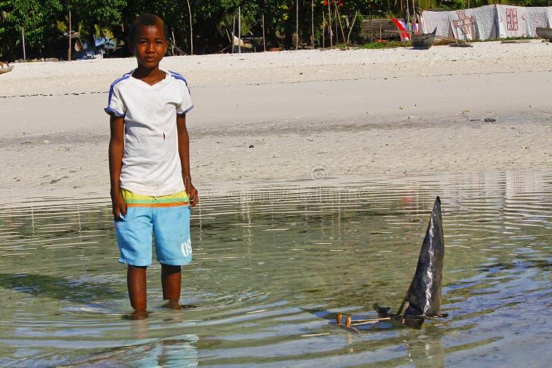 Плохой малагасийский мальчик играя с ручной работы кораблем стоковое фото rf