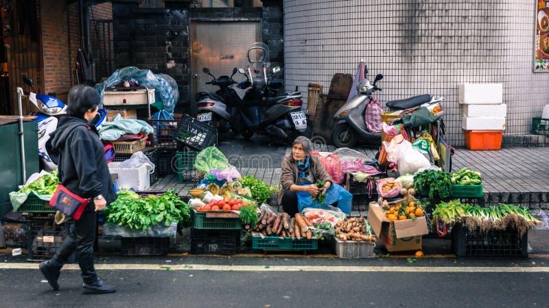 Плохой поставщик старухи продает овощи на улице Тайваня стоковые изображения