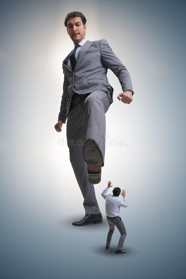 Плохой сердитый босс пиная работник в концепции дела стоковое изображение