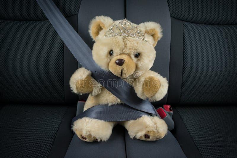Плюшевый медвежонок принцессы девушки сидит в автомобиле с тиарой стоковое фото rf