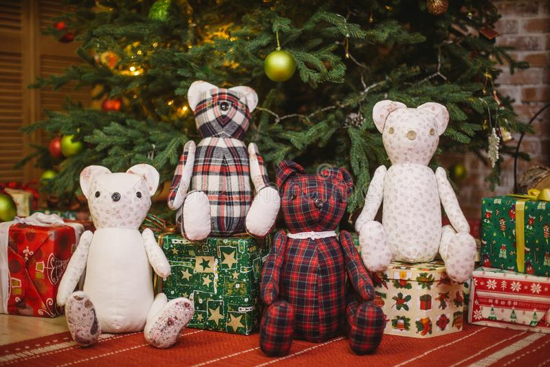 Плюшевый медвежонок сидя вниз украшенный с рождественской елкой светов с подарочными коробками стоковая фотография