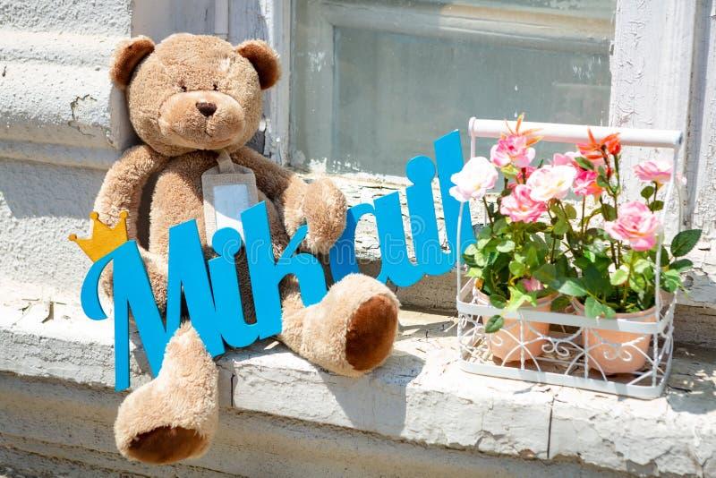 Плюшевый мишка Брауна сидя на windowsill с синью подписывает в его лапках, рядом с 2 баками цветков стоковое фото