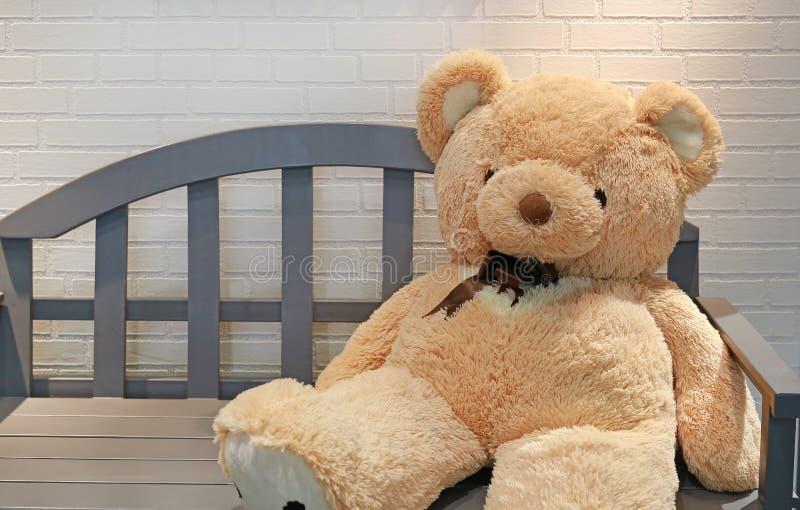 Плюшевый мишка на деревянной скамье против белой кирпичной стены стоковые фото