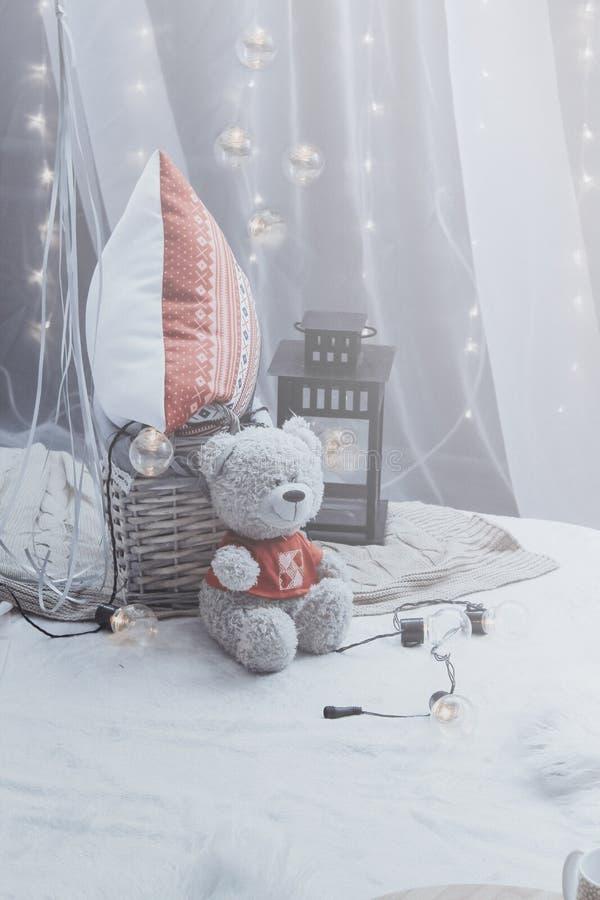 Плюшевый мишка сидя на кровати с подушками и декоративным электрофонарем никто Романтичное оформление спальни стоковая фотография rf