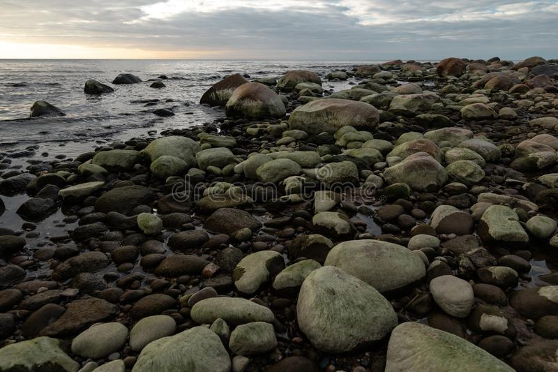 Пляж Больдэра во время пасмурного захода солнца с зеленой морской вод стоковое изображение