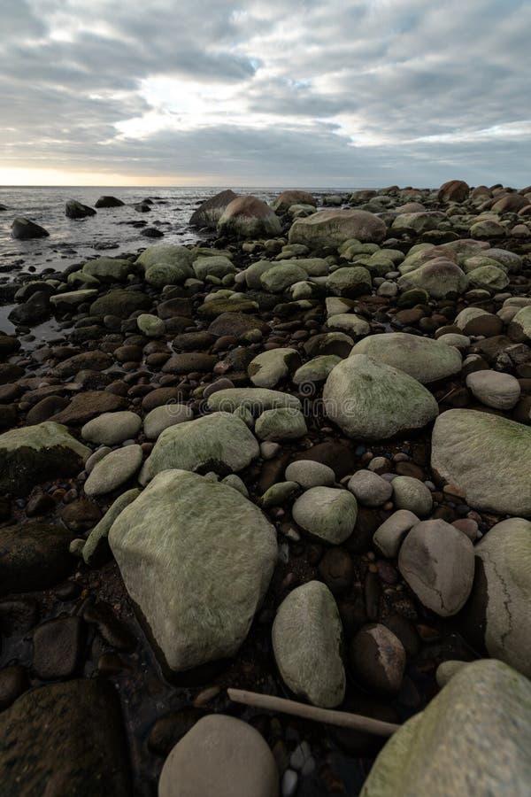 Пляж Больдэра во время пасмурного захода солнца с зеленой морской вод стоковое фото rf