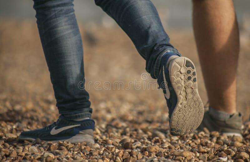 Пляж Брайтона - люди идя на камешки; ноги стоковые изображения rf