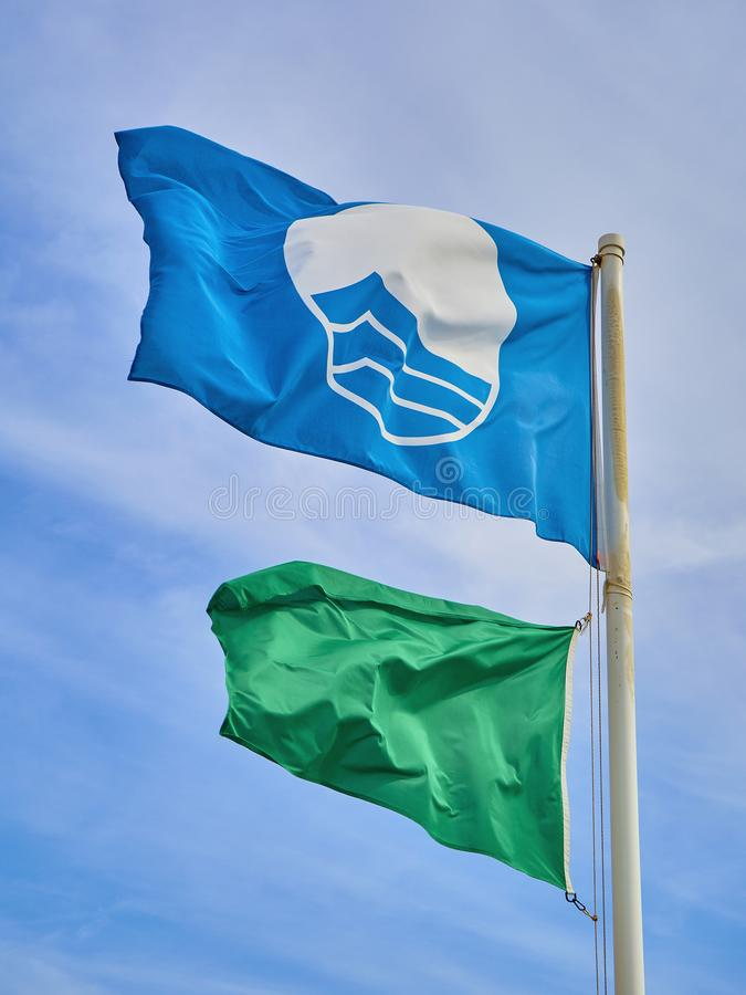 Пляж голубого флага FEEÂ и зеленый флаг личной охраны над предпосылкой голубого неба стоковые фотографии rf