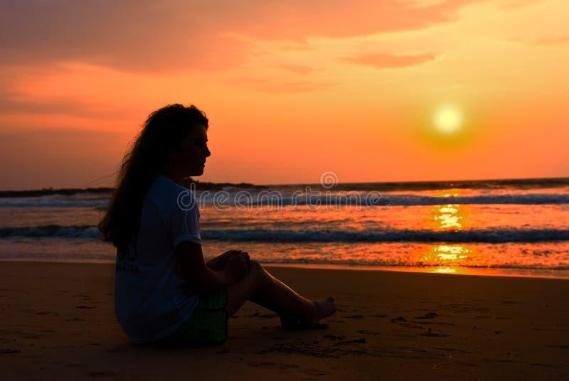пляж декабрь наслаждается девушкой силуэт ot сидит стоковое фото rf