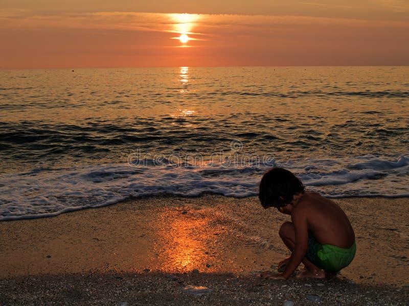 пляж играя заход солнца стоковая фотография