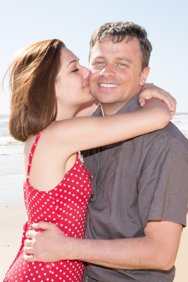 Пляж милого человека поцелуя девушки внешний стоковое изображение rf
