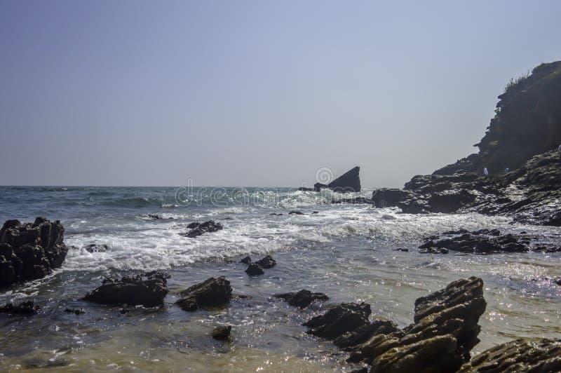 Пляж моря на заливе Индийского океана, Goa, Индии Изумрудные волны океана под голубым небом Скалистые берег и mountai концов бере стоковые изображения