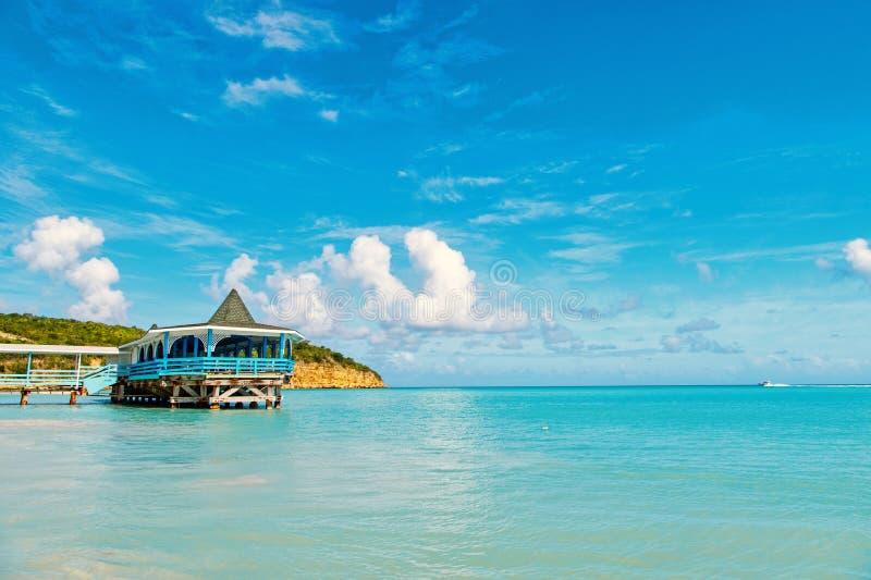 Пляж моря с деревянным укрытием на солнечный день в Антигуе Пристань в воде бирюзы на предпосылке голубого неба каникула территор стоковые фото