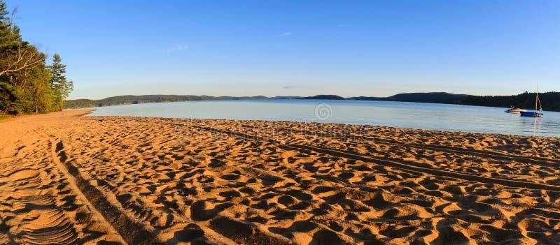 Пляж озера золотого песка с трассировками людей на заходе солнца стоковая фотография rf