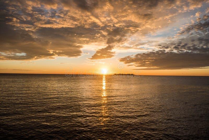 пляж после полудня последний против предпосылки голубые облака field wispy неба природы зеленого цвета травы белое стоковое фото