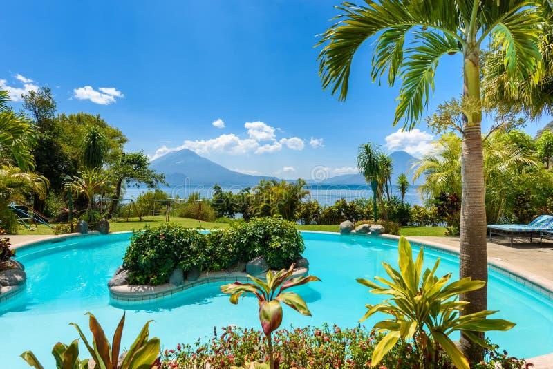 Пляж рая со стулом на озере Atitlan, Panajachel - ослабляющ и воссоздании с пейзажем ландшафта vulcano в гористых местностях  стоковое фото