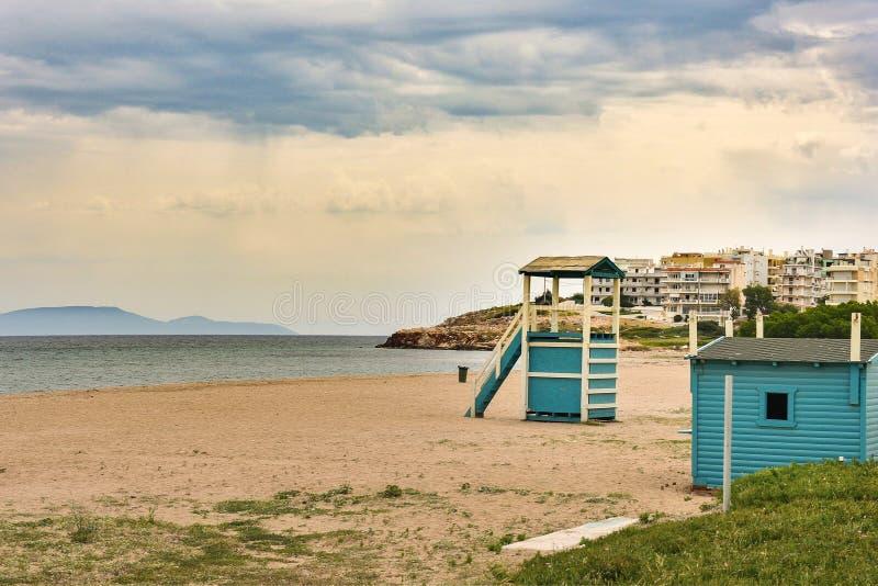 Пляж Сэнди и деревянная башня спасательной службы в городе Рафина Греция стоковое фото