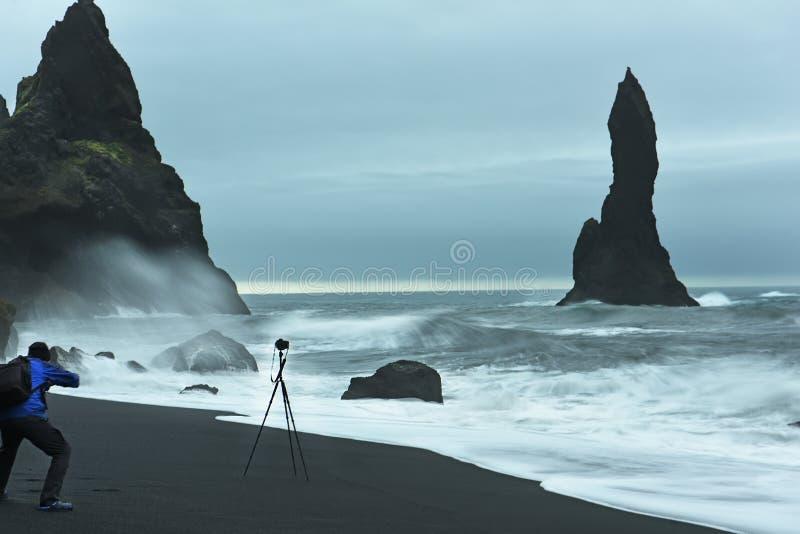 Пляж с вулканическим песком и утесы вставляя из воды Фотограф пробуя избегать от волн стоковое фото