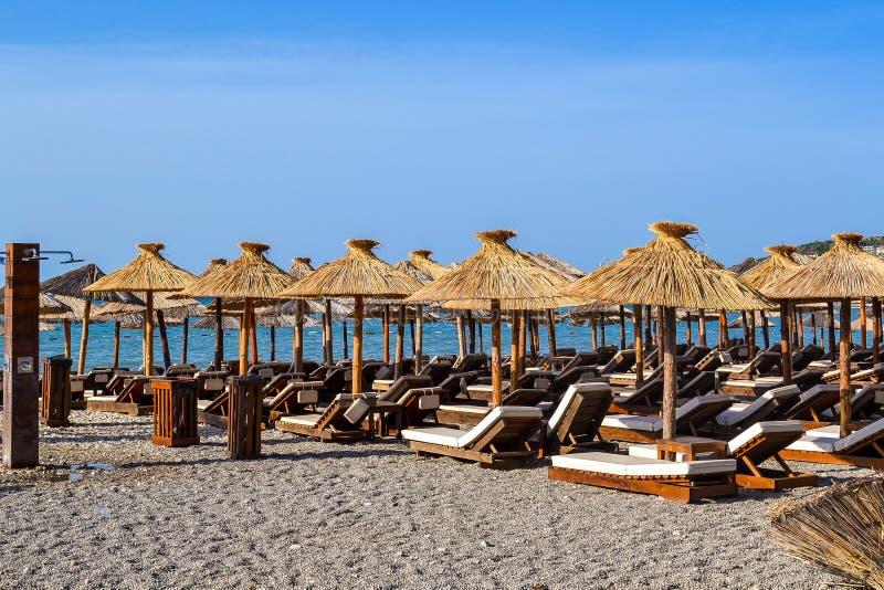 Пляж с зонтиками соломы от солнца и мягких loungers солнца Адриатическое лето побережья Без людей стоковое фото