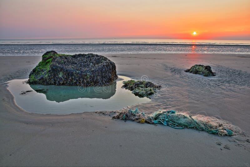 Пляж Ambleteuse на заходе солнца с красочными камнями и рыболовной сетью на переднем плане, ` Opale Коута d, шаг de Кале, Hauts d стоковые изображения rf