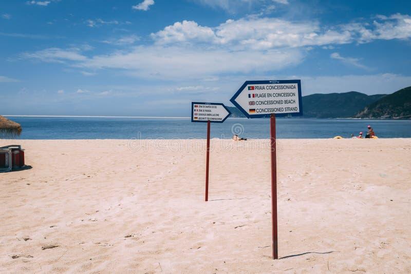 Пляж Bico das Lulas, Troia, Португалия - столбы знака показывая разъединение concessioned районов зоны стоковое изображение rf