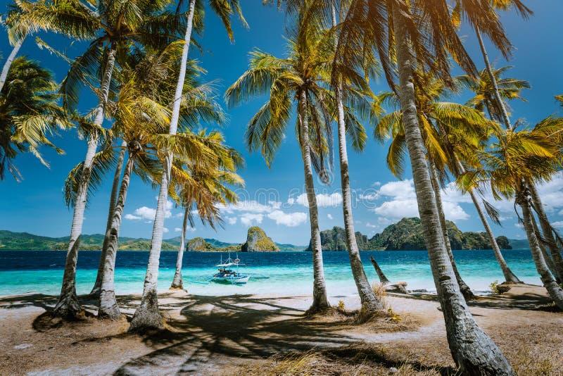 Пляж Ipil перед уникальным островом Pinagbuyatan с огромными скалами известняка и пальмами кокоса Шлюпка охмеления острова стоковое фото rf