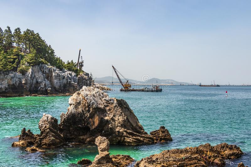 Пляж Jeungsan со скалами, промышленными кораблями и горами в предпосылке Donghae, провинция Gangwon, Южная Корея, Азия стоковое фото