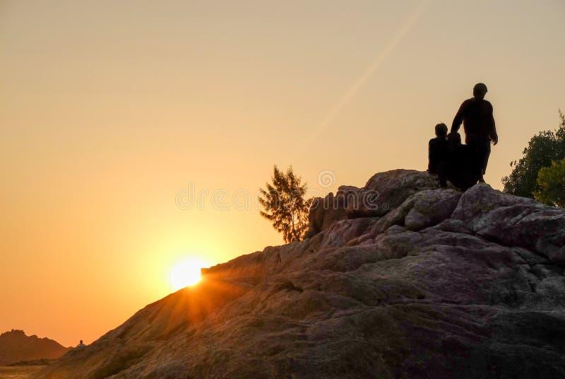 ПЛЯЖ OM, GOKARNA, KARNATAKA/INDIA-FEBUARY 2-ое, 2018: Заходящее солнце закрепляет холм утесов стоковое изображение rf