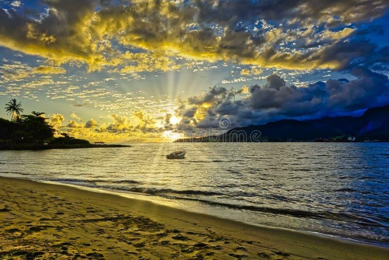 Пляж Pereque Ilhabela с шлюпкой в море на заходе солнца - Сан-Паулу, Бразилии - широкоформатное фото стоковое изображение rf