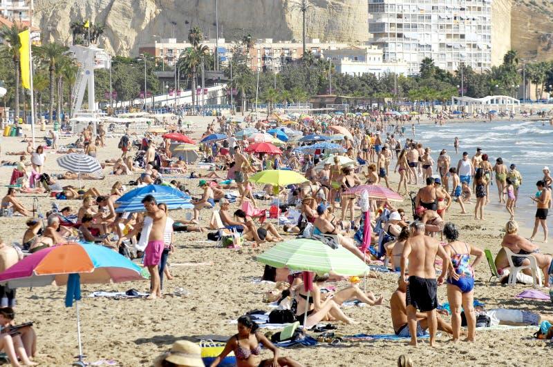 Пляж Postiguet в Аликанте полном туристов должных к хорошей погоде в месяце октября стоковое фото rf