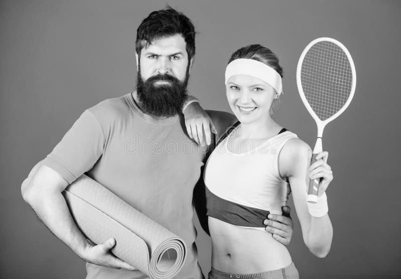 Победа и успех Sporty тренировка пар с циновкой фитнеса и ракеткой тенниса Счастливая женщина и бородатая разминка человека внутр стоковые фото