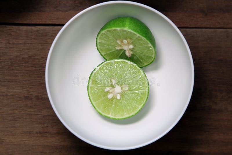 Побелите плодоовощ известью с половинным поперечным сечением в белом шаре на деревянной предпосылке, подготовьте еду стоковые фото