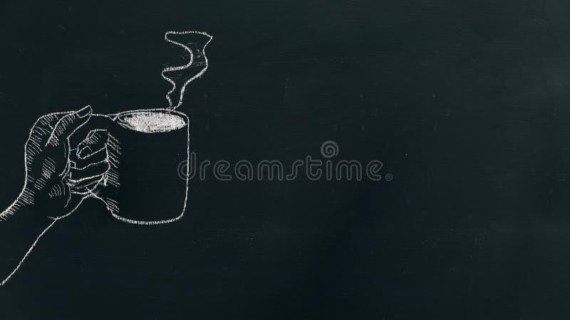 Побелите руку мелом рисуя руку держа кофейную чашку с паром на черной доске на левой стороне рамки стоковые изображения