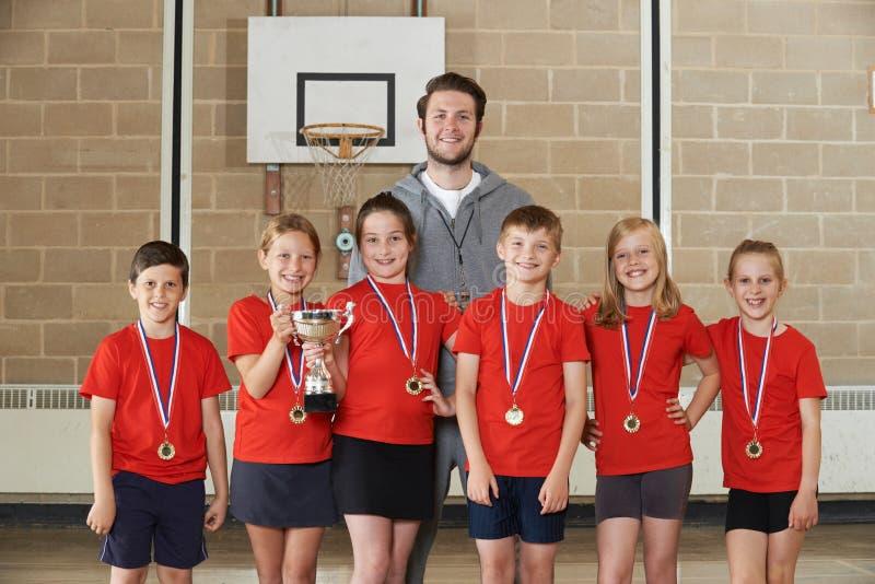 Победоносная спортивная команда школы с медалями и трофеем в спортзале стоковое изображение rf