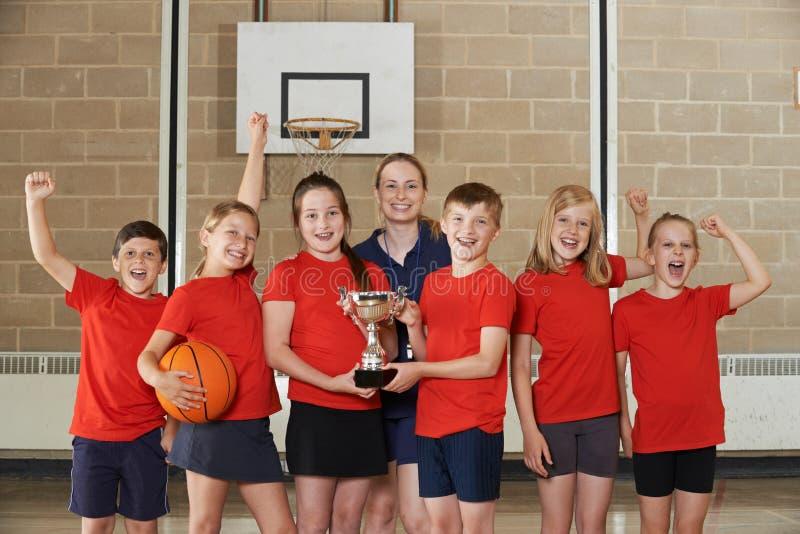Победоносная спортивная команда школы с трофеем в спортзале стоковые изображения