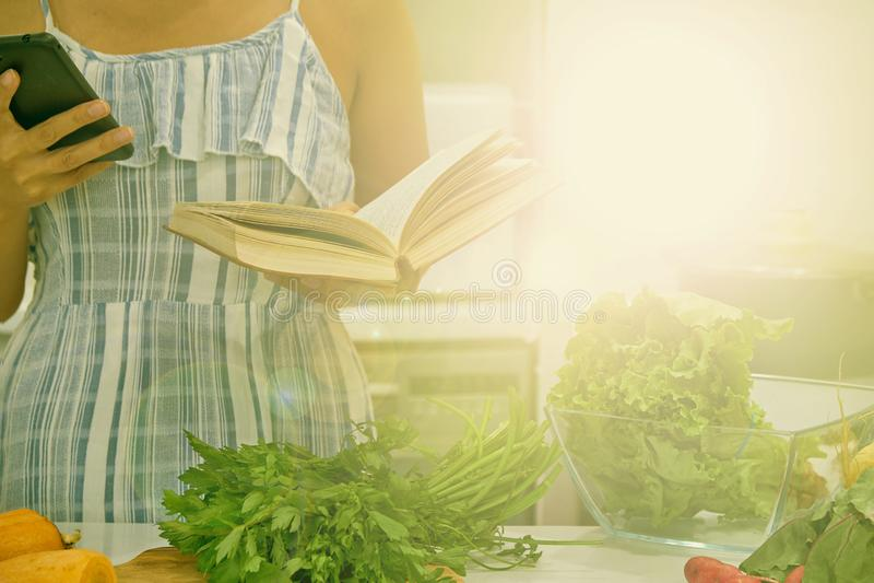 Поваренная книга чтения молодой женщины в кухне, ища рецепт стоковые изображения rf